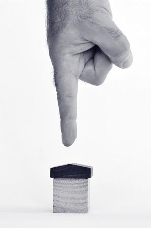 homeownership: Man finger point at a toy house on white background - copy space.Concept photo of real estate business, home  Insurance, house rental,buying, renting, mortgage, finance,service and repair costs (BW)