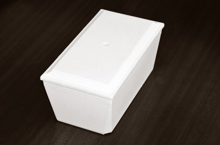 cremated: White funeral urn in coffin shape complete view isolated on dark wooden background.Philosophical concept photo of life ,death, cremation, reincarnation, spiritual , religious , soul ,spirit and spirituality.