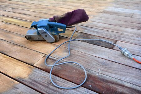 Working tool,  sander,  on old wooden deck. Concept photo, background texture image with copy- space