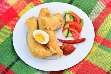 jewish home: Classic Yemeni Jachnun, a classic Jewish Yemeni meal of Jachnun, grated tomatos, boiled egg, red hot pepper and salad. Usually served for breakfast or lunch on shabbat (Saturday). Stock Photo