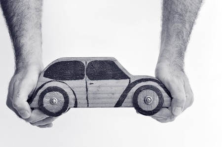 Renting: Hands and toy car isolated on white background - copy space.Concept photo of car business, car Insurance, auto dealership,car rental ,safe driving ,buying, renting, fuel, service and repair costs (BW)