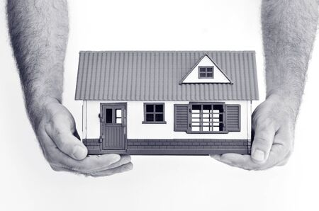 homeownership: Man hands holds toy house isolated on white background - copy space.Concept photo of real estate business, home Insurance, house rental,buying, renting, mortgage, finance,service and repair costs (BW) Stock Photo