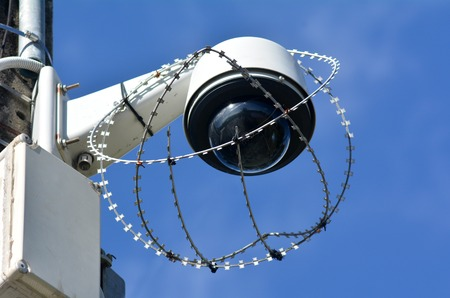 closed circuit: One security surveillance camera protected with barbed wire against vandalism and crime. concept photo of security.
