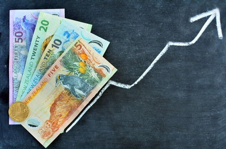 new economy: New Zealand Dollar Banknotes on upward trend arrow. Concept photo of money, banking ,currency and foreign exchange rates.  (Isolated on white background) Stock Photo