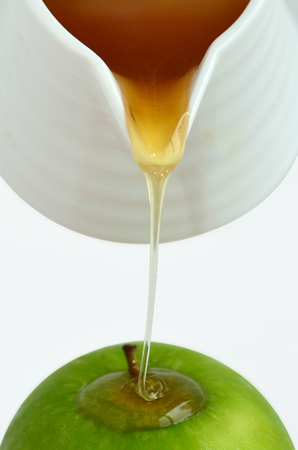jewish holiday: Fresh honey drop from honey pot on green apple during Rosh Hashanah Jewish holiday, on white background with copy space