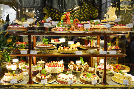 Pastry shop display window with variety of cakes.