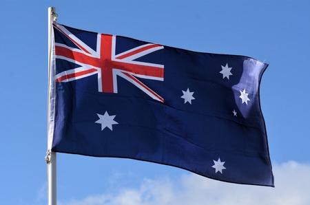 The National flag of Australia against blue sky.