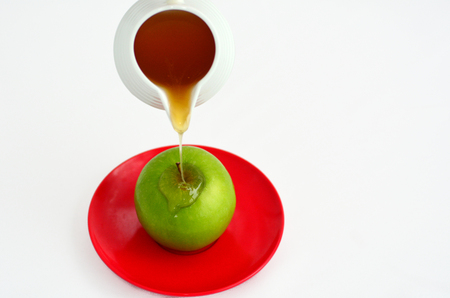 honey pot: Fresh honey drop from honey pot on green apple during Rosh Hashanah Jewish holiday, on white background with copy space