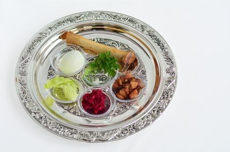 ユダヤ人の休日の過越でセダー食事中に使用される第 7 の象徴的な項目と過越祭セダー プレート。白の背景コピー スペースに 写真素材