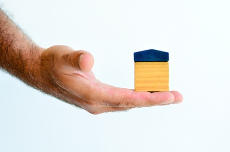 homeownership: Man hand holds toy house isolated on white background with copy space.Concept photo of real estate business, home  Insurance, house rental,buying, renting, mortgage, finance,service and repair costs