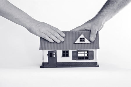 homeownership: Couple touch a toy house isolated on white background - copy space.Concept photo of real estate business, home  Insurance, house rental,buying, renting, mortgage, finance,service and repair costs (BW)