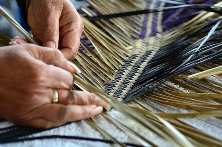 Handen van een oude Maori vrouw weven een traditionele Maori-geweven kunstwerk.