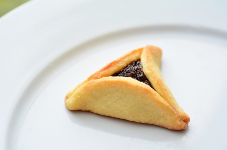 hamantashen: One backed Hamentashen, Ozen Haman, Purim cookie on a white plate for the Jewish holiday Purim.(Copy space)