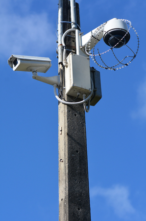 closed circuit: Two security surveillance cameras on a high pole at the park.concept photo of security.