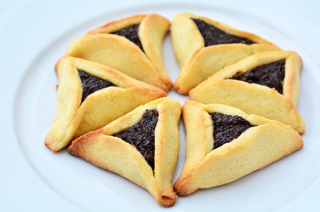 hamantash: Six Backed Hamentashen, Ozen Haman, Purim cookies designed in Hexagon shape on a white plate for the Jewish holiday Purim.