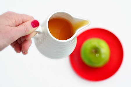 honey pot: Jewish woman hand holds honey pot and ready to pour fresh honey with on green apple during Rosh Hashanah Jewish holiday, on white background with copy space