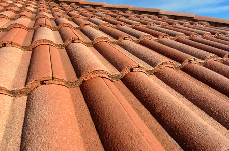 spanish tile: Spanish style ceramic tile roof with blue sky and whit clouds sunny day. Background texture Stock Photo