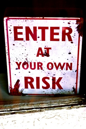 window display: Buissness sign enter at your own risk on shop display window
