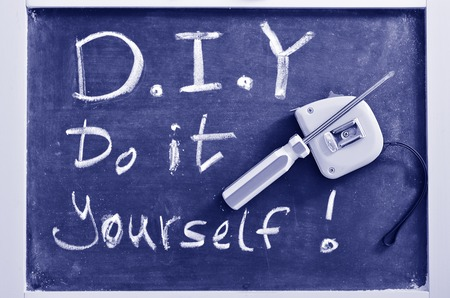 do it yourself: Do It Yourself - D.I.Y , Handwritten with white chalk on a blackboard with working tools.concept photo of Do It Yourself.