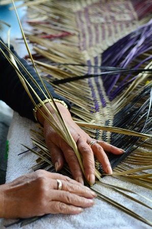 Hands of an old Maori woman weaving a traditional Maori woven artwork.