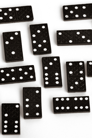unrelated: Domino effect concept scattered domino tiles on white background.copyspace. Vertical BW