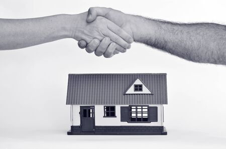 homeownership: Man and a woman shaking hands over a toy house on white background - copy space.Concept photo of real estate business, home  Insurance, house rental, buying, renting, mortgage, selling, finance. (BW) Stock Photo
