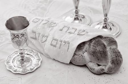 shabat: Mesa de v�spera de Shabat con pan jal� cubierto, velas sab�ticas y Kidush taza de vino. (BW) Foto de archivo