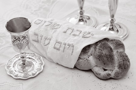jewish home: Shabbat eve table with covered challah bread, Sabbath candles and Kiddush wine cup. (BW) Stock Photo