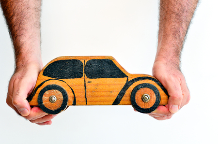 safe driving: Hands holds toy car isolated on white background with copy space.Concept photo of car business, car Insurance, auto dealership,car rental ,safe driving ,buying, renting, fuel, service and repair costs Stock Photo