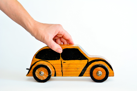 safe driving: Woman hands holds toy car isolated on white background-copy space.Concept photo of car business,car Insurance, auto dealership,car rental ,safe driving ,buying, renting, fuel, service and repair costs Stock Photo