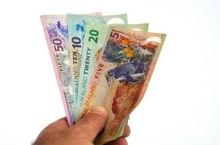 cash money: Sirve la mano que sostiene billetes de banco Dólar de Nueva Zelanda. Foto del concepto de las tasas monetarias, bancarias, monetarias y de cambio extranjero. (Aisladas sobre fondo blanco)
