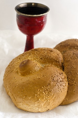 challah: A concept photo of challah bread for the Jewish observance of Shabbat with a glass of wine in the background.