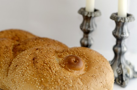shabbat: A concept photo of challah bread for the Jewish observance of Shabbat with candles in the background.