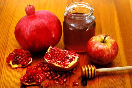 jewish food: Traditional jewish food, apple, honey and pomegranate for the holiday of Rosh Hashanah are isolated on white.