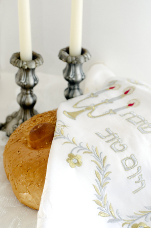 observance: A concept photo of covered challah bread for the Jewish observance of Shabbat with candles in the background. Stock Photo