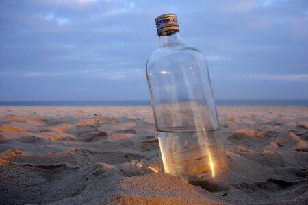 onto: Bottle washed onto shore.