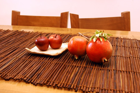 jewish home: Traditional apples and pommegranate (rimon) on a table for the Jewish holiday of Rosh Hashanah (new year). Stock Photo