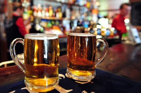 barra de bar: Dos tazas de cerveza en un pub en Nueva Zelanda.