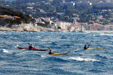 people in row: People row kayaks over Calanques in south  France.
