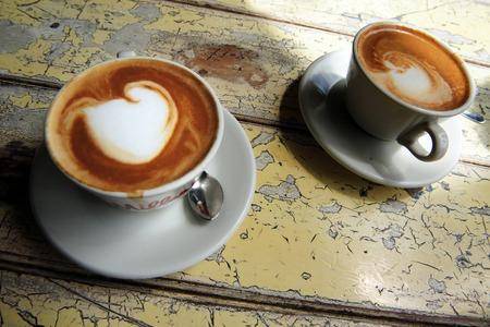 Tasses de café blanc plat chaud boit sur une vieille table en bois dans un café.