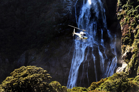 A helicopter flies over Fiordland, southern New Zealand. Banque d'images