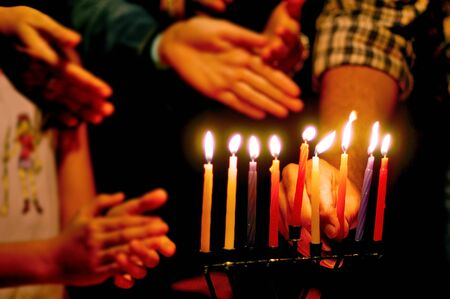 A family is lighting a candle for the Jewish holiday of Hanukkah that is observed for eight nights and days.