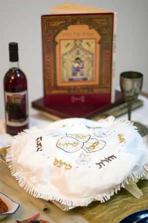 religious text: Table prepared with blessings, red grape juice and the religious text (haggadah) for the Jewish holiday of Passover