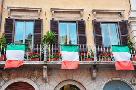 italian landscape: Identical apartment windows each hanging Italian flags in Rome, Italy