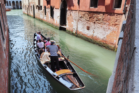 gondolier: A gondolier rowing with a gondola in venice, Italy.