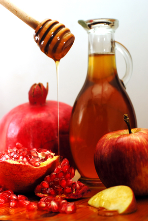 apple and honey: Traditional jewish food, apple, honey and pomegranate for the holiday of Rosh Hashanah are isolated on white.