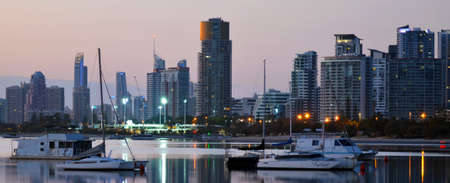 Sail boats: Panoramic view of sail boats under Surfers Paradise CBD skyline at dusk in Gold Coast Queensland, Australia.