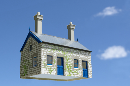 housing industry: Toy house hover in the air aginst blue sky . Concept photo of Real estate market bubble , booming, money,price, rent, grid, home, house, housing, industry and subprime mortgage crisis. (Copy Space).