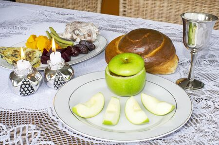 challah: Jewish New Year - Rosh Hashanah , apple with honey, candles ,challah , wine cup and blessings on the Seder table.