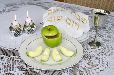 challah: Jewish New Year - Rosh Hashanah , apple with honey, candles ,challah and wine cup on the Seder table.